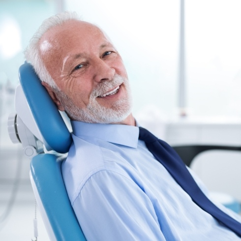 Man in dental chair smiling after dental implant tooth replaceemtn