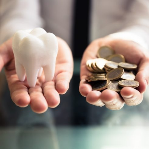 Hands holding a model tooth and pile of coins