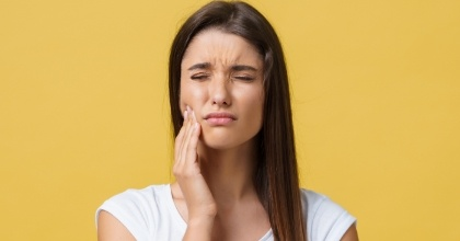 Woman in need of restorative dentistry holding cheek